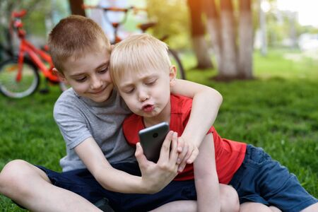 Two boys using a smartphone are sitting on the grass. Bicycles in the background