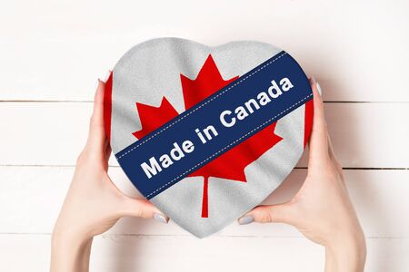 Inscription Made in Canada, the flag of Canada. Female hands holding a heart shaped box. White wooden table on a background. Place for text