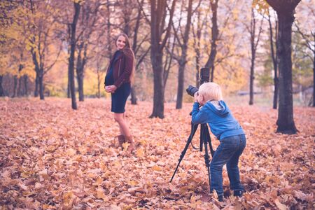 Little blond boy with a large reflex camera on a tripod. Photographs a pregnant woman. Family photo session Zdjęcie Seryjne - 128901410