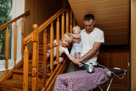 Father with a small child in his arms, the eldest son reaches for an electric iron. Home safety