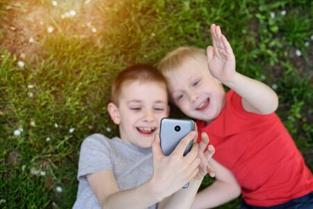 Two boys make selfie on a smartphone while lying on the grass. Top view Zdjęcie Seryjne - 128901441