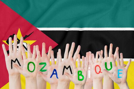 Inscription Mozambique on the childrens hands against the background of a waving flag of the Mozambique Stockfoto