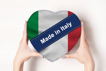 Inscription Made in Italy, the flag of Italy. Female hands holding a heart shaped box. White background. Stock fotó