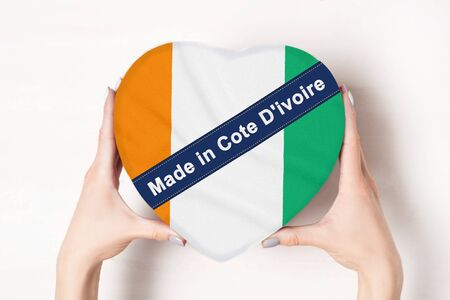 Inscription Made in Cote dIvoire the flag of Cote dIvoire. Female hands holding a heart shaped box. White background.
