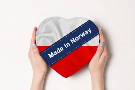 Inscription Made in Poland the flag of Poland. Female hands holding a heart shaped box. White background.