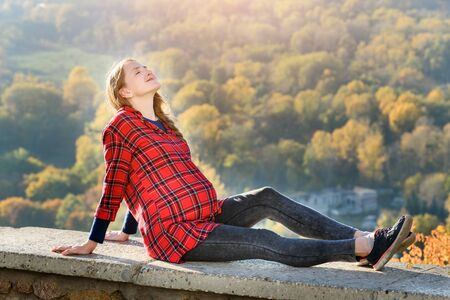 Pregnant woman lies on a hill with her eyes closed. Meditation. Autumn forest on the background