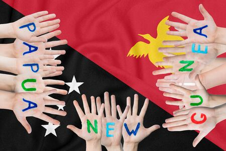 Inscription Papua New Guinea on the childrens hands against the background of a waving flag of the Papua New Guinea