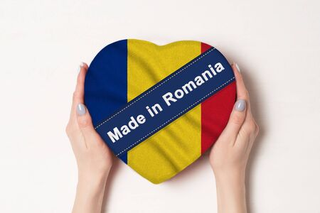 Inscription Made in Romania the flag of Romania. Female hands holding a heart shaped box. White background.