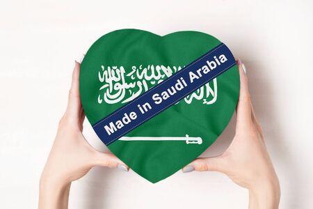Inscription Made in Saudi Arabia the flag of Saudi Arabia. Female hands holding a heart shaped box. White background.