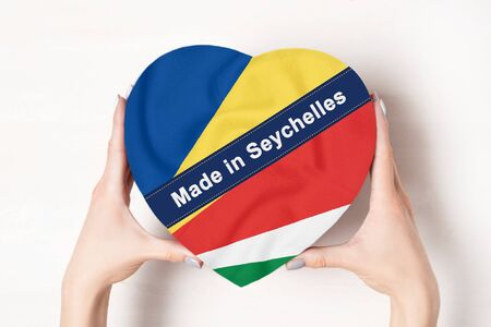 Inscription Made in Seychelles the flag of Seychelles. Female hands holding a heart shaped box. White background. Stock fotó