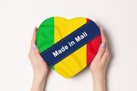 Inscription Made in Mali the flag of Mali. Female hands holding a heart shaped box. White background.
