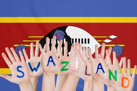 Inscription Swaziland on the childrens hands against the background of a waving flag of the Swaziland Stockfoto