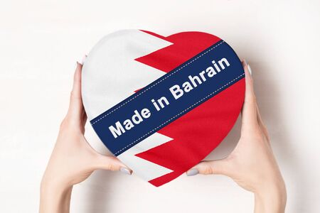 Inscription Made in Bahrain the flag of Bahrain. Female hands holding a heart shaped box. White background.