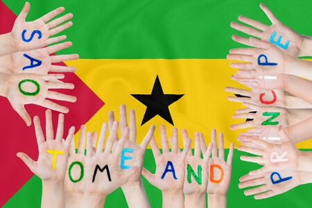 Inscription Sao Tome and Principe on the childrens hands against the background of a waving flag of the Sao Tome and Principe