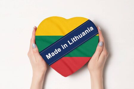 Inscription Made in Lithuania the flag of Lithuania. Female hands holding a heart shaped box. White background.