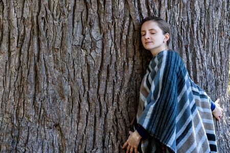 Young woman leaning against the trunk of a large tree. Closed eyes. Unity with nature