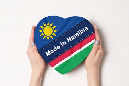 Inscription Made in Namibia the flag of Namibia. Female hands holding a heart shaped box. White background. Stock fotó