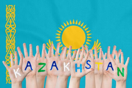 Inscription Kazakhstan on the childrens hands against the background of a waving flag of the Kazakhstan