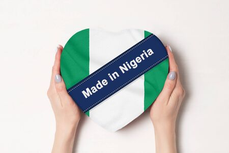 Inscription Made in Nigeria the flag of Nigeria . Female hands holding a heart shaped box. White background.