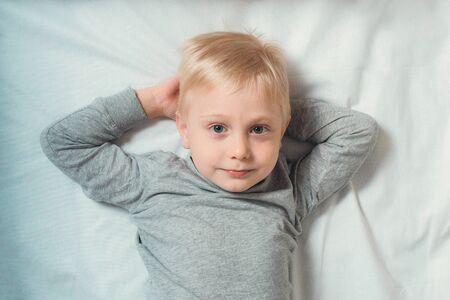 Blond cute boy lies hands behind his head. White background