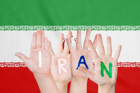 Inscription Iran on the childrens hands against the background of a waving flag of the Iran Stockfoto