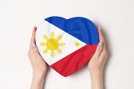 Flag of Philippines on a heart shaped box in a female hands. White background