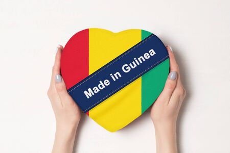 Inscription Made in Guinea the flag of Guinea. Female hands holding a heart shaped box. White background.
