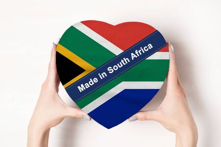 Inscription Made in South Africa the flag of South Africa. Female hands holding a heart shaped box. White background.