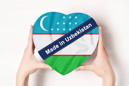 Inscription Made in Uzbekistan the flag of Uzbekistan. Female hands holding a heart shaped box. White background.