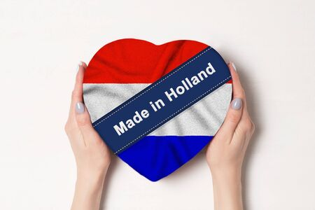 Inscription Made in Holland the flag of Holland. Female hands holding a heart shaped box. White background. Stock fotó