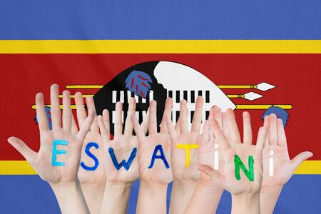 Inscription Eswatini on the childrens hands against the background of a waving flag of the Eswatini