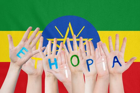 Inscription Ethiopia on the childrens hands against the background of a waving flag of the Ethiopia Stockfoto