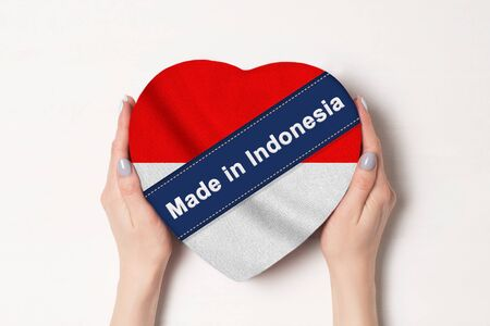 Inscription Made in Indonesia the flag of Indonesia. Female hands holding a heart shaped box. White background.