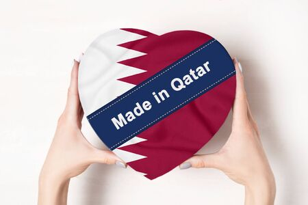 Inscription Made in Qatar the flag of Qatar. Female hands holding a heart shaped box. White background.