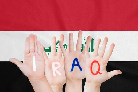 Inscription Iraq on the childrens hands against the background of a waving flag of the Iraq