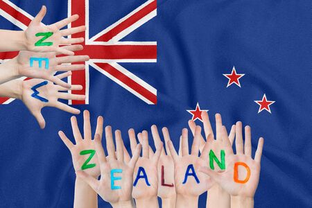 Inscription New Zealand on the childrens hands against the background of a waving flag of the New Zealand 写真素材
