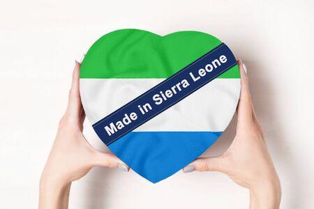 Inscription Made in Sierra Leone the flag of Sierra Leone. Female hands holding a heart shaped box. White background. Stock fotó