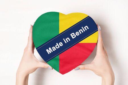 Inscription Made in Benin the flag of Benin. Female hands holding a heart shaped box. White background.