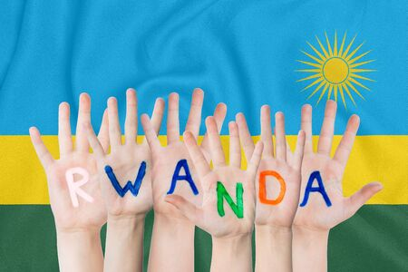 Inscription Rwanda on the childrens hands against the background of a waving flag of the Rwanda