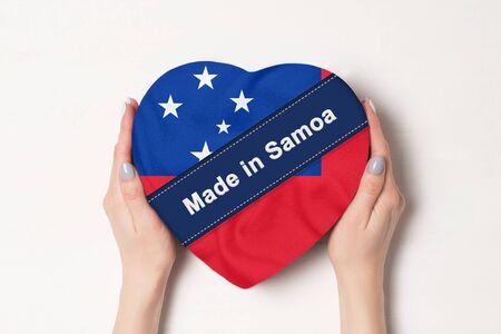 Inscription Made in Samoa the flag of Samoa. Female hands holding a heart shaped box. White background. Stock fotó