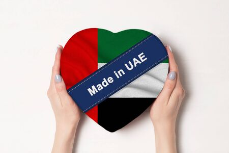 Inscription Made in United Arab Emirates the flag of United Arab Emirates. Female hands holding a heart shaped box. White background. Stock fotó