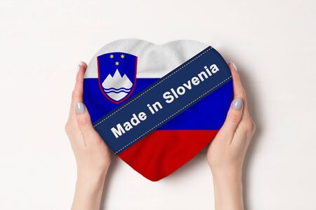 Inscription Made in Slovenia the flag of Slovenia. Female hands holding a heart shaped box. White background. Imagens