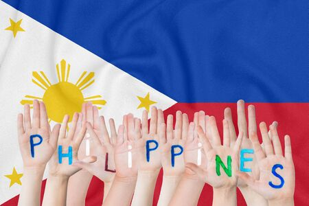 Inscription Philippines on the childrens hands against the background of a waving flag of the Philippines