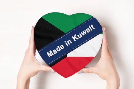 Inscription Made in Kuwait, the flag of Kuwait. Female hands holding a heart shaped box. White background.