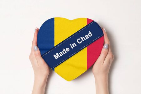 Inscription Made in Chad the flag of Chad. Female hands holding a heart shaped box. White background.