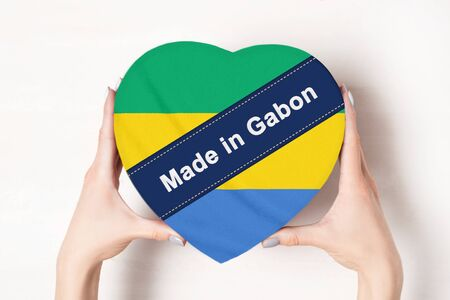 Inscription Made in Gabon, the flag of Gabon. Female hands holding a heart shaped box. White background.