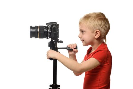 Blond boy shoots video on DSLR camera. Side view. White background, isolate Banco de Imagens