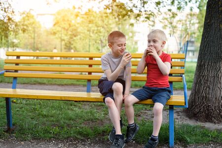 Two boys have a snack on a bench in the park and chat. Summer day