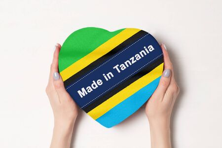 Inscription Made in Tanzania the flag of Tanzania. Female hands holding a heart shaped box. White background.
