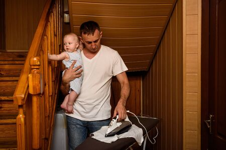 Father with a small baby in her arms ironed linen. Doing housework 写真素材
